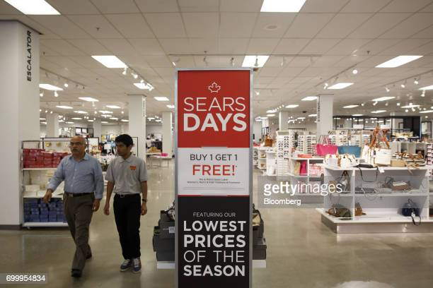 Shoppers walk past a 'Buy 1 Get 1 Free' sign displayed at a Sears Canada Inc store inside a mall in Toronto Ontario Canada on Thursday June 22 2017...