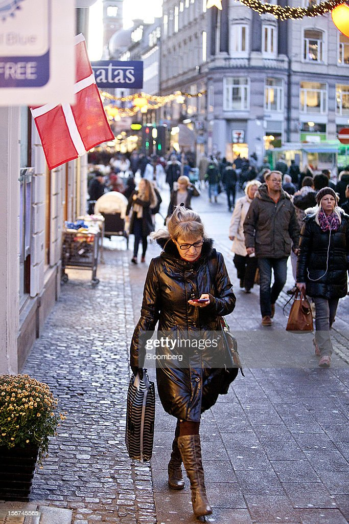 Shoppers walk past a Danish flag hanging outside a store on Stroget in central Copenhagen, Denmark, on Monday, Nov. 19, 2012. Denmark's two-year yields sank to the lowest in almost three months in Copenhagen trading as Europe's debt crisis continues to drive investors north. Photographer: Linus Hook/Bloomberg via Getty Images