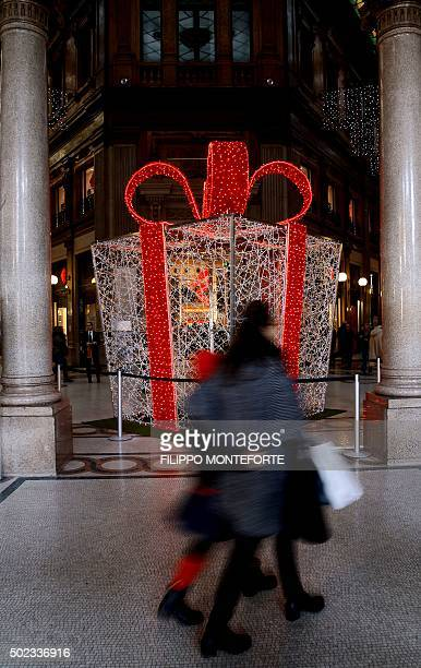 Shoppers walk past a decoration in the form of a giant gift box at the 'Galleria Colonna' shopping mall in Rome on December 23 2015 / AFP / FILIPPO...