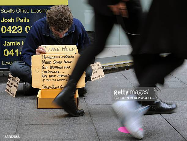 Shoppers walk past a homeless ma begging along a pavement n in Sydney on December 8 2011 Australia's unemployment rate unexpectedly rose to 53...