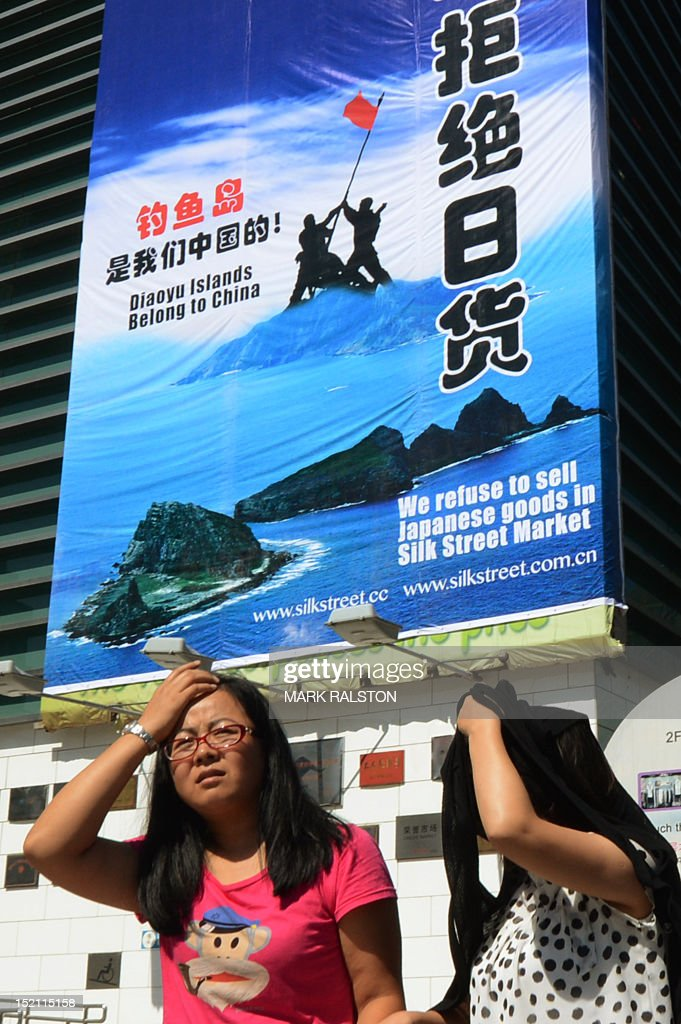 Shoppers walk past a large protest banner at the Silk Street market, which is famous for selling counterfeit designer brand goods, as anti-Japanese protests continue in Beijing over the Diaoyu islands issue, known as the Senkaku islands in Japanese, on September 17, 2012. Japan and China, Asia's two largest economies, are at loggerheads over the archipelago in the East China Sea administered by Tokyo under the name Senkaku and claimed by China under the name Diaoyu. AFP PHOTO/Mark RALSTON