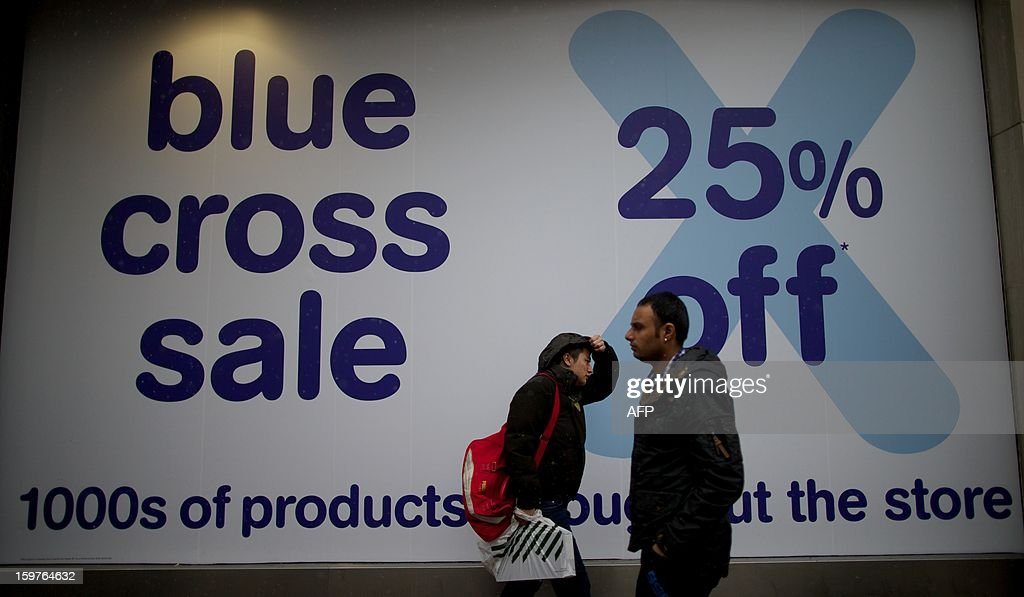 Shoppers walk past a sale sign at a branch of troubled music retail chain HMV on Oxford Street in central London on January 20, 2013. Four big British high-street retailers had to call in administrators this winter as cash-strapped, web-literate consumers proved unforgiving of stores failing to adapt to fast-evolving markets.AFP PHOTO/ANDREW COWIE