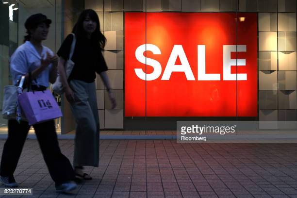 Shoppers walk past a sale sign displayed at a Hennes Mauritz AB store in Osaka Japan on Wednesday July 26 2017 Japan is scheduled to release June's...