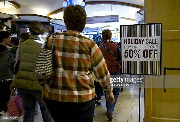 Shoppers walk past a sale sign in front of a store at the Westfield Mall in Annapolis Maryland on Black Friday 23 November 2007 AFP PHOTO/Jim WATSON