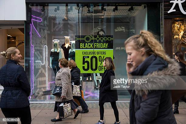 Shoppers walk past a sign for Black Friday deals outside a shop on Oxford Street on November 22 2016 in London England British retailers have begun...