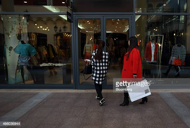 Shoppers walk past a store at the Florentia Village outlet shopping mall operated by Fingen SpA in Tianjin China on Wednesday March 11 2015 China's...
