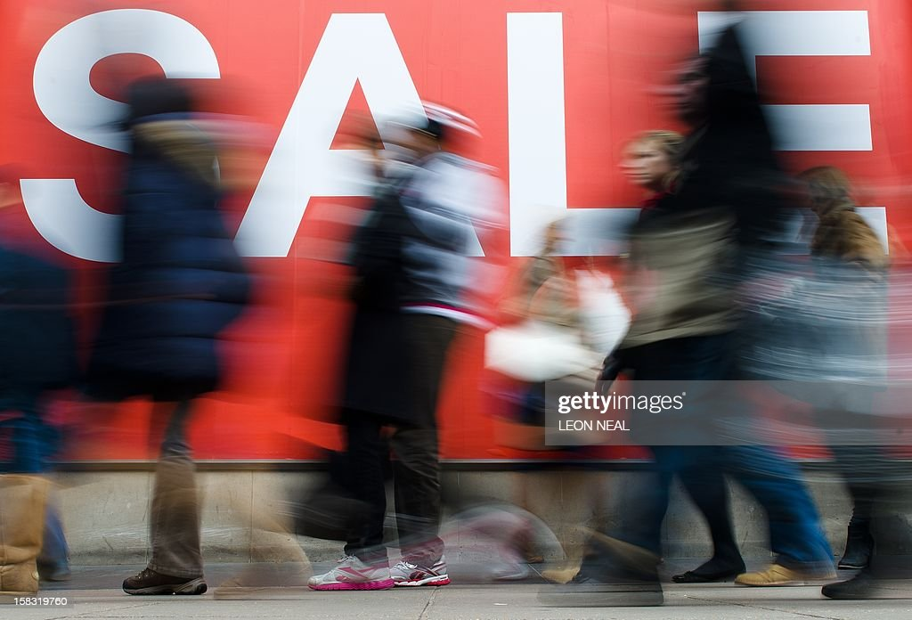 Shoppers walk past a store sale sign on Oxford Street in central London on December 13, 2012. Store in London's West End have enjoyed brisk trade in recent weeks as shoppers from other European nations have flocked to the British capital for Christmas shopping. AFP PHOTO/Leon Neal