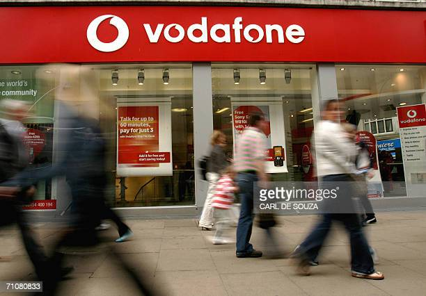 Shoppers walk past a Vodafone store in London 30 May 2006 Vodafone the world's biggest mobile phone company reported today the biggest annual net...