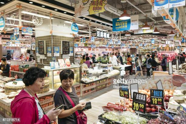 Shoppers walk past advertisements for Ant Financial Services Group's Alipay an affiliate of Alibaba Group Holding Ltd hanging above stalls inside MC...