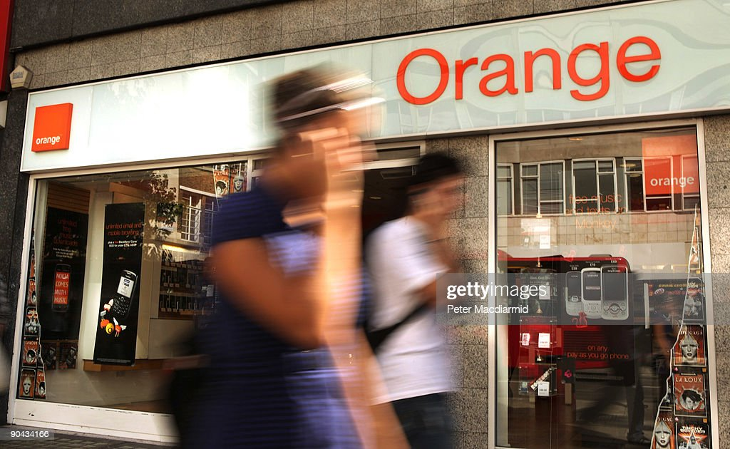 Shoppers walk past an Orange shop in Oxford Street on September 8, 2009 in London, England. Mobile phone companies Orange and T-Mobile have anounced plans to merge their United Kingdom operations. This will create the UK's biggest mobile operator with a customer base of 28 million users.