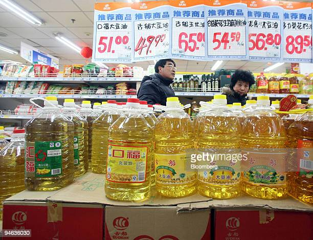 Shoppers walk past bottles of soybean oil at a supermarket in Beijing China on Monday Dec 17 2007 China the world's biggest vegetable oil consumer...