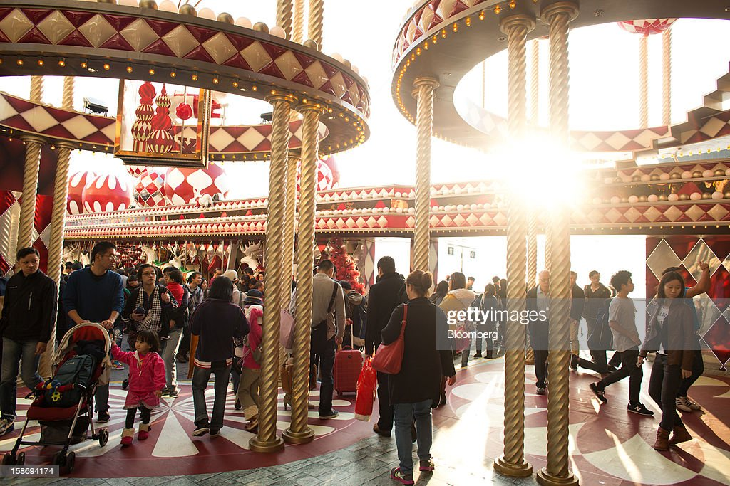 Shoppers walk past Christmas decorations at the entrance to a shopping mall in the Tsim Sha Tsui area of Hong Kong, China, on Saturday, Dec. 22, 2012. Hong Kong's economy is set for its weakest annual expansion since the global financial crisis as the European sovereign debt crisis damps global trade. Photographer: Lam Yik Fei/Bloomberg via Getty Images
