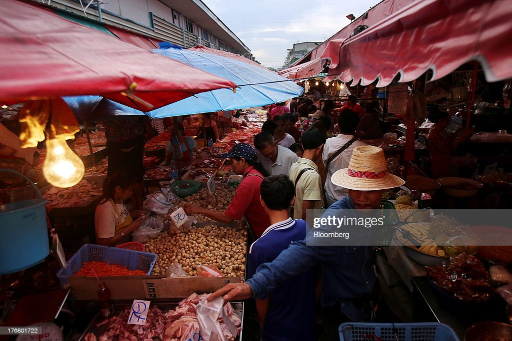 Shoppers walk past food stalls at the Klong Thoei market in Bangkok, Thailand, on Sunday, Aug. 18, 2013. Thai economic growth slowed for a second quarter as exports cooled and local demand weakened, with rising household debt restricting the scope for monetary easing. Photographer: Dario Pignatelli/Bloomberg via Getty Images