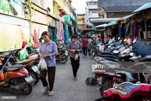 Shoppers walk past parked motorcycles near a food market in Nan Nan Province Thailand on Friday March 3 2017 After more than a year of disinflation...