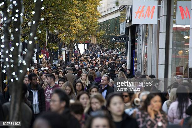 Shoppers walk past retail stores on Oxford Street on 'Black Friday' in London on November 25 2016 Black Friday is a sales offer originating from the...