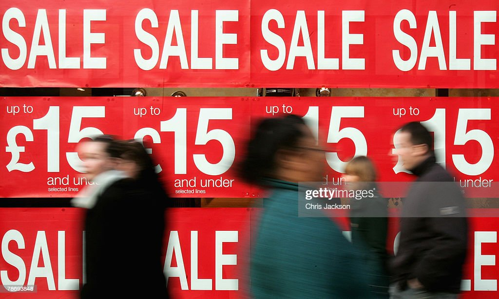Shoppers walk past Sale posters on Oxford Street on January 2, 2008 in London, England. Shops are preparing to announce their results after the Christmas trading period.