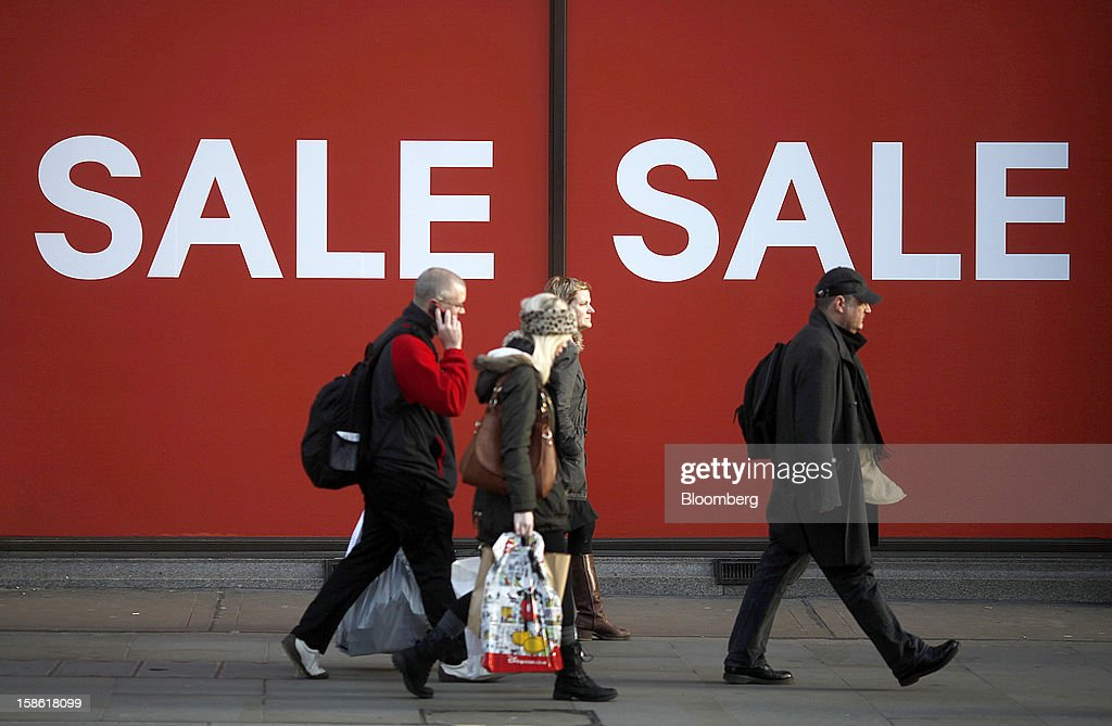 Shoppers walk past sale signs displayed outside an Hennes & Mauritz AB (H&M) store on Regents Street in London, U.K., on Friday, Dec. 21, 2012. Britain's economy expanded less than previously estimated in the third quarter and the budget deficit unexpectedly widened in November, complicating Prime Minister David Cameron's attempts to bolster the recovery. Photographer: Simon Dawson/Bloomberg via Getty Images