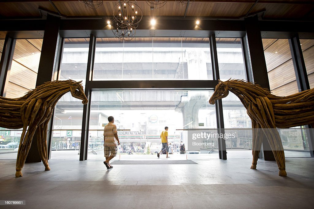Shoppers walk past sculptures as they exit the Siam Center shopping mall in Bangkok, Thailand, on Tuesday, Feb. 5, 2013. Thai inflation may average 2.8 percent this year, the Bank of Thailand said. Photographer: Brent Lewin/Bloomberg via Getty Images