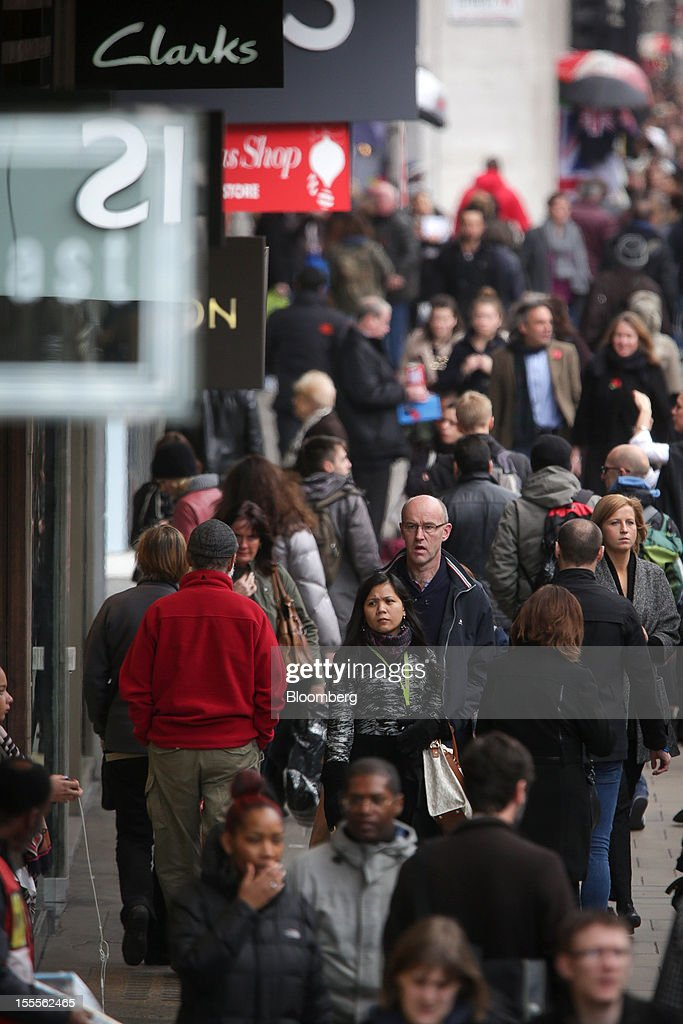 Shoppers walk past stores on Oxford Street in central London, U.K., on Monday, Nov. 5, 2012. Britain exited a double-dip recession in the third quarter with the strongest growth in five years as Olympic ticket sales and a surge in services helped boost the rebound. Photographer: Jason Alden/Bloomberg via Getty Images
