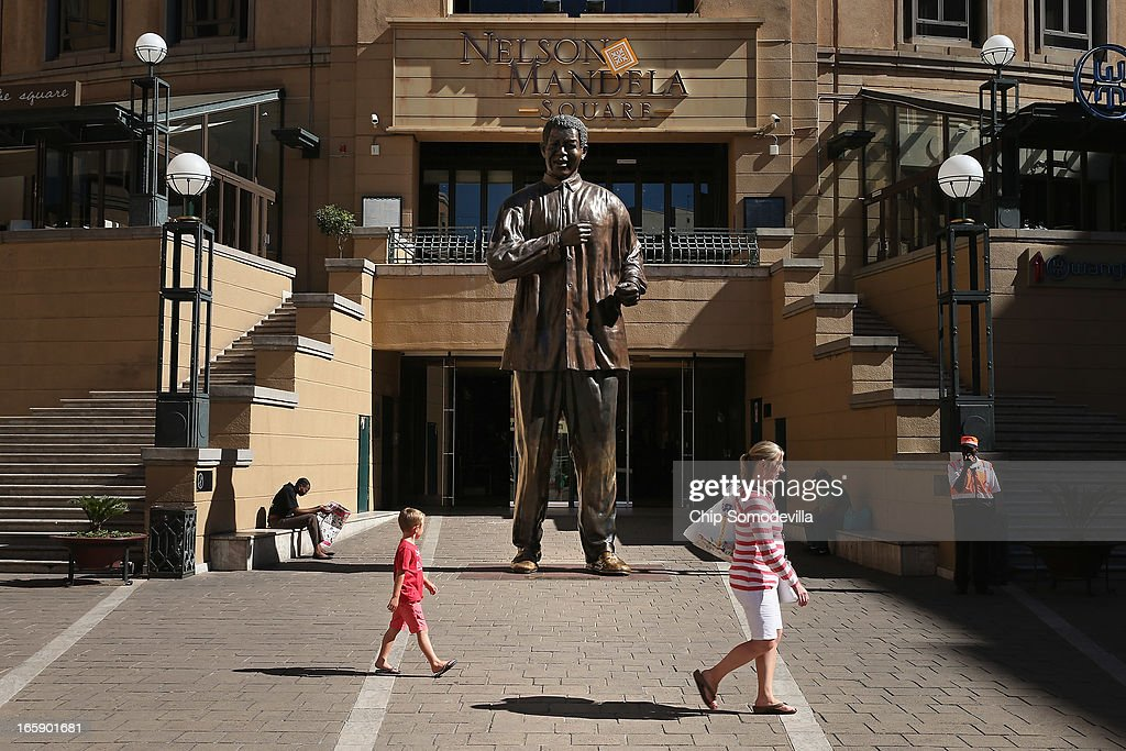 Shoppers walk past the 20-foot-tall statue of former South African President Nelson Mandela in Mandela Square near the Sandton shopping district on April 7, 2013 in Johannesburg, South Africa. Mandela returned to his Johannesburg home yesterday after spending nine days in the hospital with pneumonia.