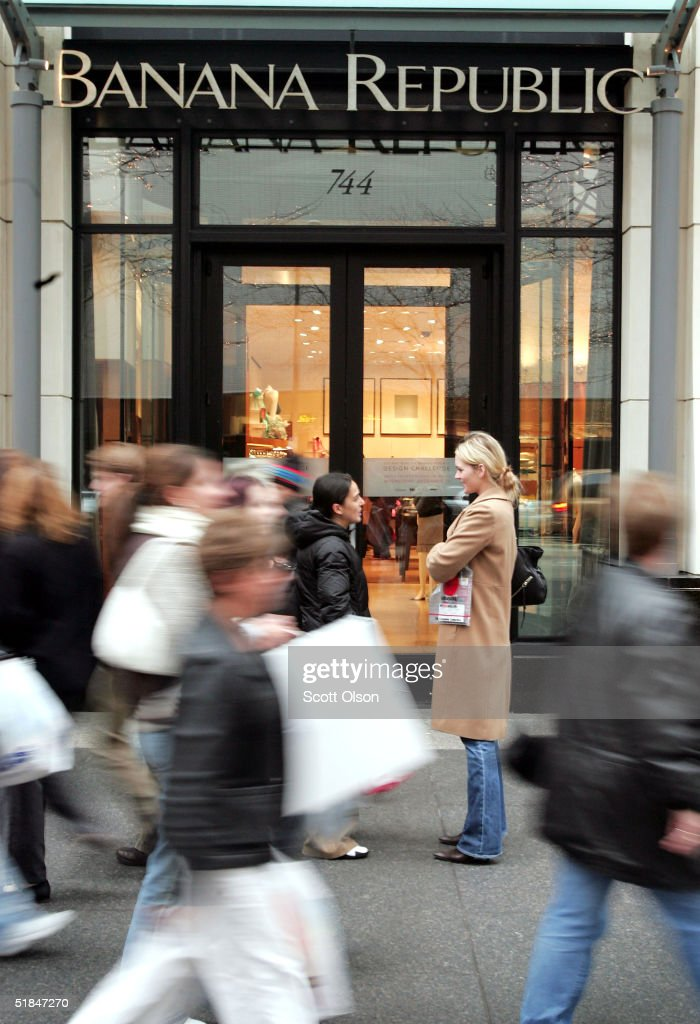 Shoppers walk past the Banana Republic store in the Michigan Avenue shopping district December 10 2004 in Chicago Illinois US consmer confidence...