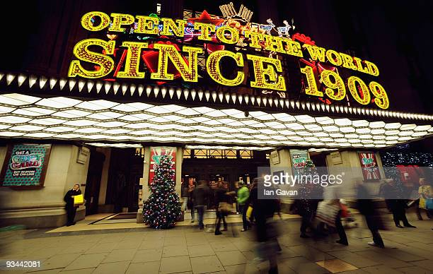 Shoppers walk past the Christmas themed main entrance of Selfridges department store in Oxford Street on November 26 2009 in London England
