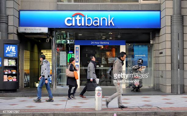 Shoppers walk past the entrance to a Citibank branch facility in Tokyo's trendy Shibuya district