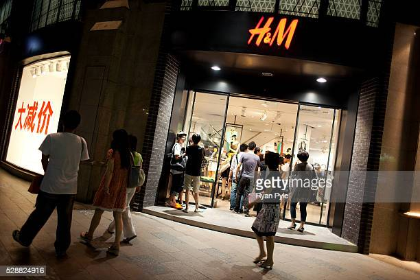 Shoppers walk past the entrance to HM along Huai Hai Road one of the main shopping districts in Shanghai China