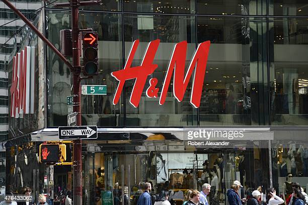 Shoppers walk past the entrance to the HM clothing store on Fifth Avenue in Midtown Manhattan in New York City New York