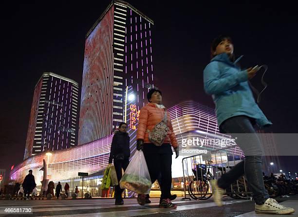 Shoppers walk past the Tongzhou Wanda Plaza shopping mall operated by Dalian Wanda Group Co at night in Beijing China on Saturday March 14 2015...