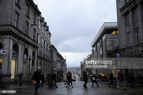 Shoppers walk the streets in central Aberdeen Scotland on January 21 2015 On the docks in Aberdeen oil workers put a brave face on hundreds of job...