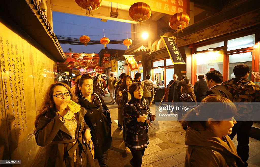 Shoppers walk through a market at night in Beijing, China, on Wednesday, March 6, 2013. China maintained its economic-growth target at 7.5 percent for 2013 while setting a lower inflation goal of 3.5 percent, setting up a challenge for new leaders to keep prices in check without harming expansion. Photographer: Tomohiro Ohsumi/Bloomberg via Getty Images