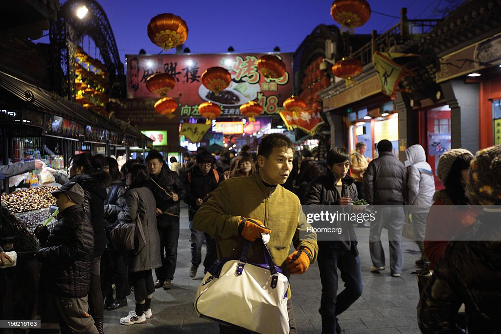 Shoppers walk through a shopping district in Beijing, China, on Sunday, Nov. 11, 2012. China's retail sales exceeded forecasts and inflation unexpectedly cooled to the slowest pace in 33 months, signaling the government is boosting growth without driving a rebound in prices. Photographer: Tomohiro Ohsumi/Bloomberg via Getty Images