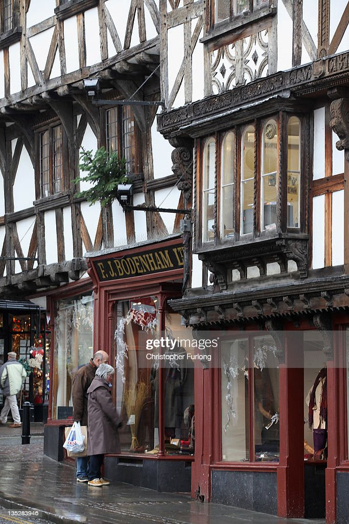 Shoppers walk through the rural town of Ludlow in Shropshire on December 8, 2011 in Ludlow, England. With a weak outlook at the start of the Christmas shopping boom, many retailers are slashing prices with the hopes of combating poor sales.
