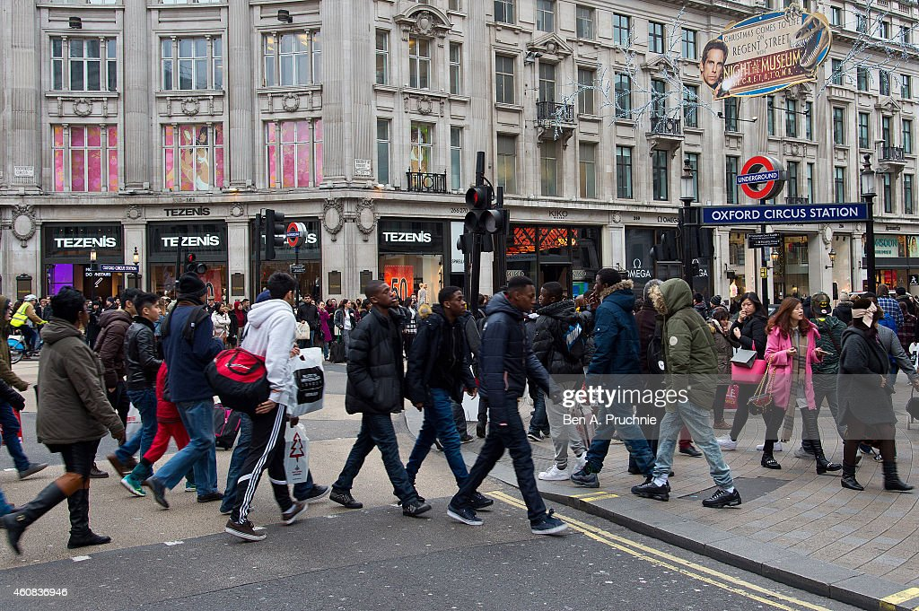 Shoppers walk to stores on Oxford Street during the annual boxing day sales on December 26 2014 in London England