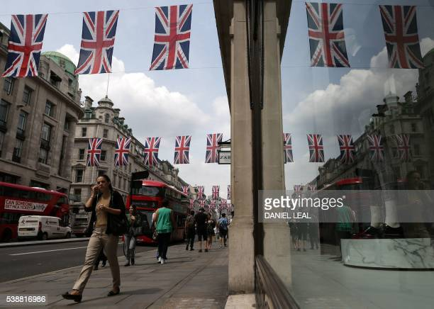 Shoppers walk underneath British Union flags hanging above Regent Street in central London on June 8 as Britain prepares to celebrate the 90th...
