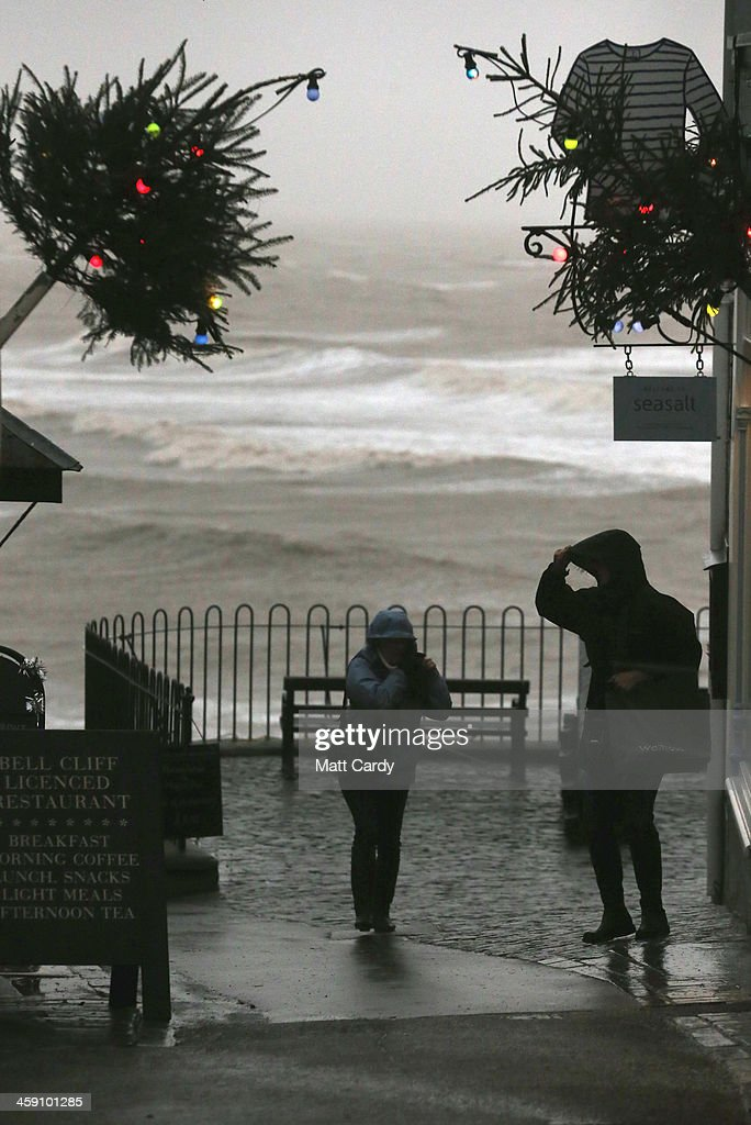 Shoppers walk up the high street as they experience stormy weather on December 23, 2013 in Lyme Regis, England. The Met Office has issued a number of severe weather warnings for heavy rain and high winds and is warning that it may lead to some travel disruption as people make their journeys for Christmas.