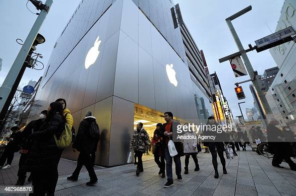 Shoppers walking past Apple store at the highend shopping district of Ginza in Tokyo Japan on February 07 2015