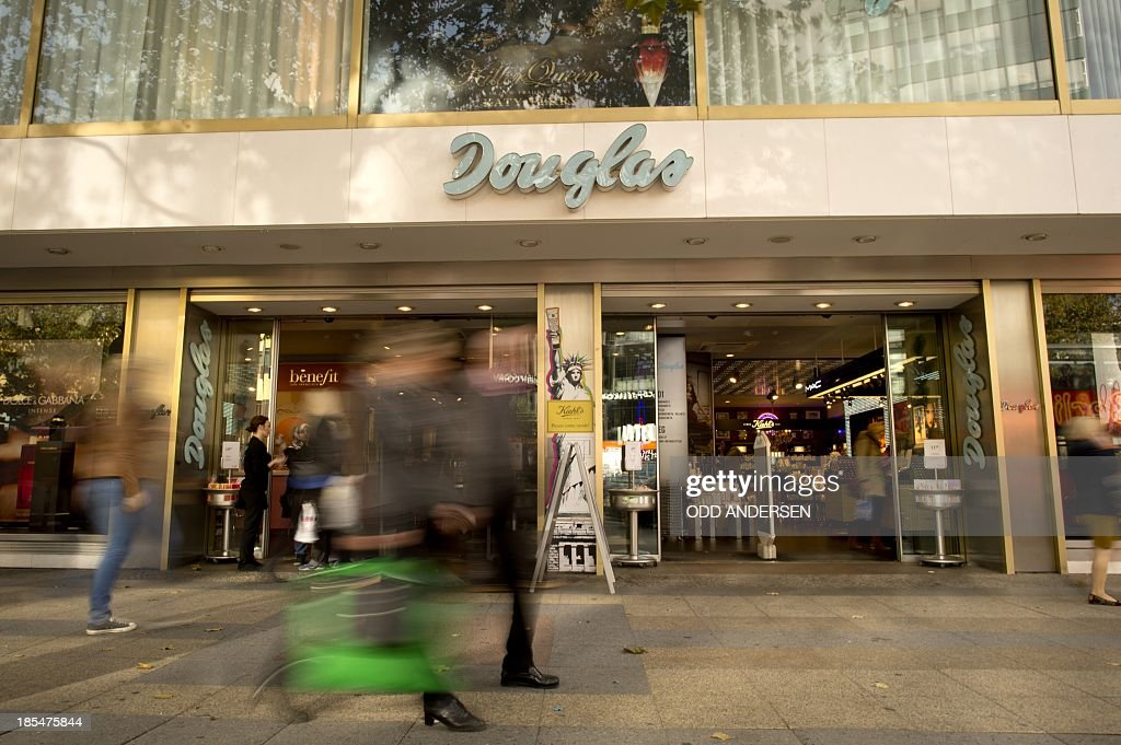Shoppers walks past one of the outlets of cosmetics chain 'Douglas' in Berlin on October 21, 2013. The German cosmetics retailer Douglas Holding is in talks to buy the French perfumery chain Nocibe in a deal that would make it France's largest branch network, according to the company's informations.