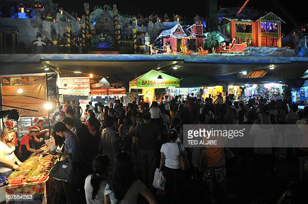 Shoppers watch a Christmas show inside a night market near a mall in Manila on December 13 2010 Too many holidays are forcing many potential...