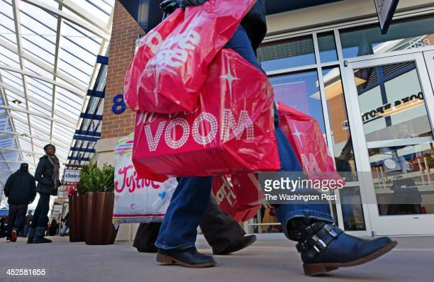 Shoppers weilding bags walk from store to store at the new Tanger Outlet Mall at National Harbor in Oxon Hill MD on November 29 2013 Today's...