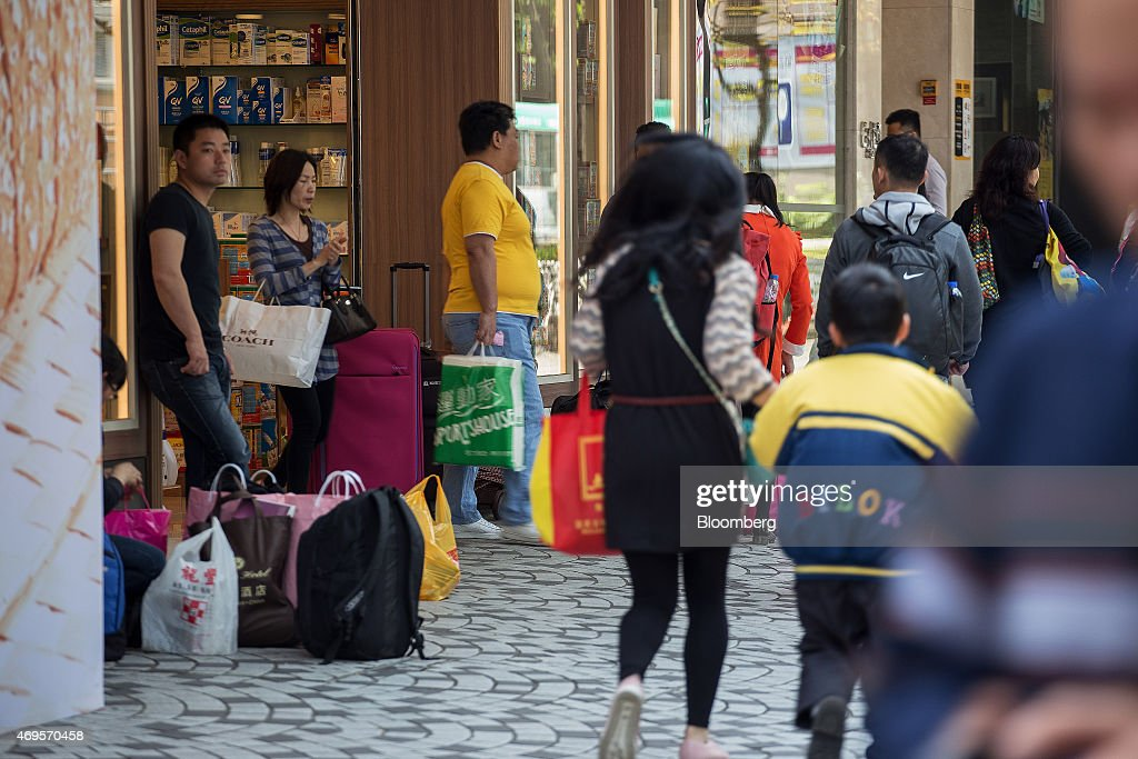 Shoppers with shopping carts and shopping bags stand outside a pharmacy store in the Sheung Shui district near the border with mainland China in Hong...