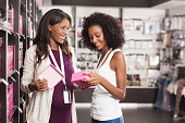 Beauty consultant pregnant woman helping to young girl customer at beauty shop. Seller showing her pink gift box.