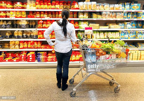 shopping at the supermarket customer with shopping cart in front of supermarket shelves