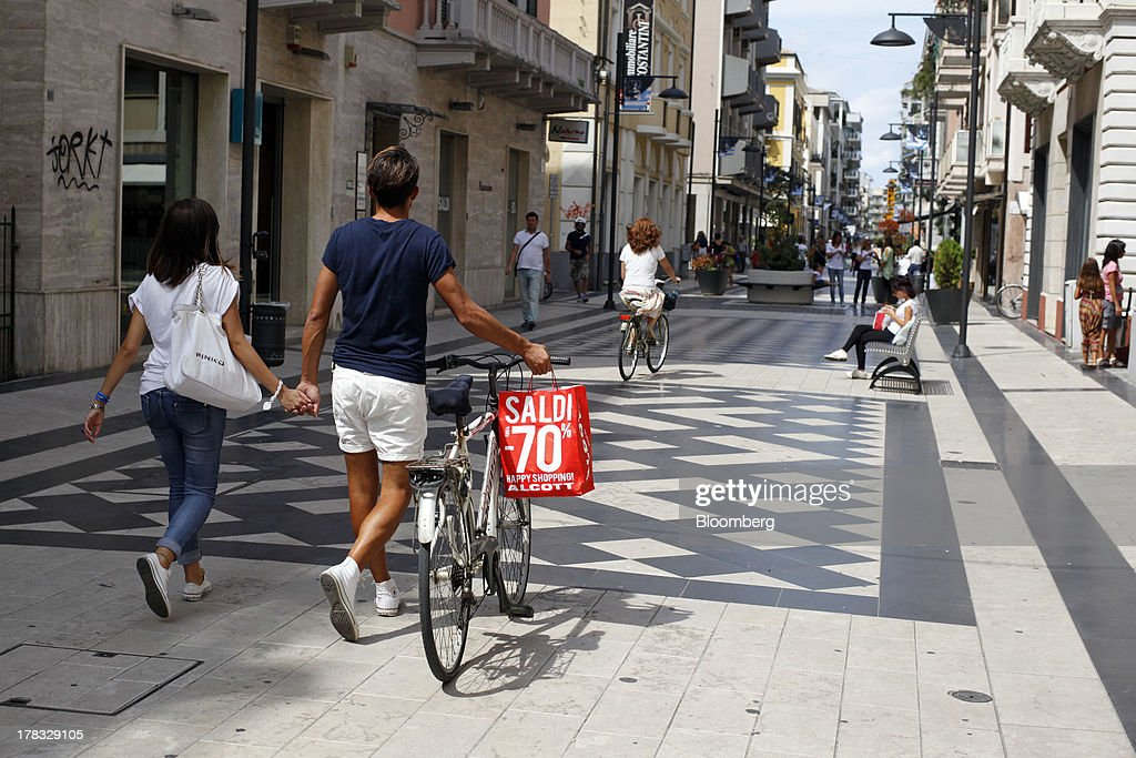 A shopping bag advertising a discount sale hangs from the handlebars of a bicycle as a pedestrian walks beside it in Pescara, Italy, on Thursday, Aug. 29, 2013. Italian consumer confidence rose this month more than economists expected as households grew optimistic amid expectations that the government would cut a property tax. Photographer: Marc Hill/Bloomberg via Getty Images