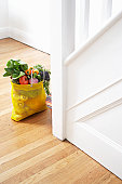 Shopping bag with fresh vegetables on floor