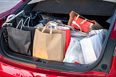 many shop bags in car trunk shopping concept