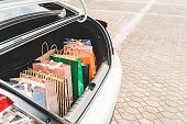 Shopping bags in car trunk with copy space. Modern shopping lifestyle, rish people or leisure activity concept
