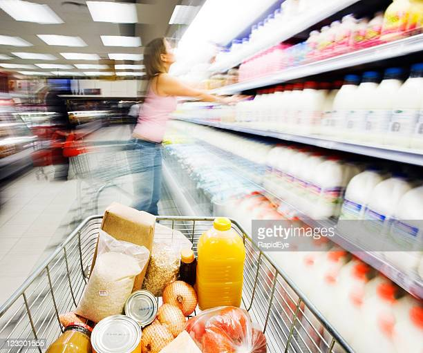 Shopping cart alongside dairy fridge. Motion blur obscures contents.