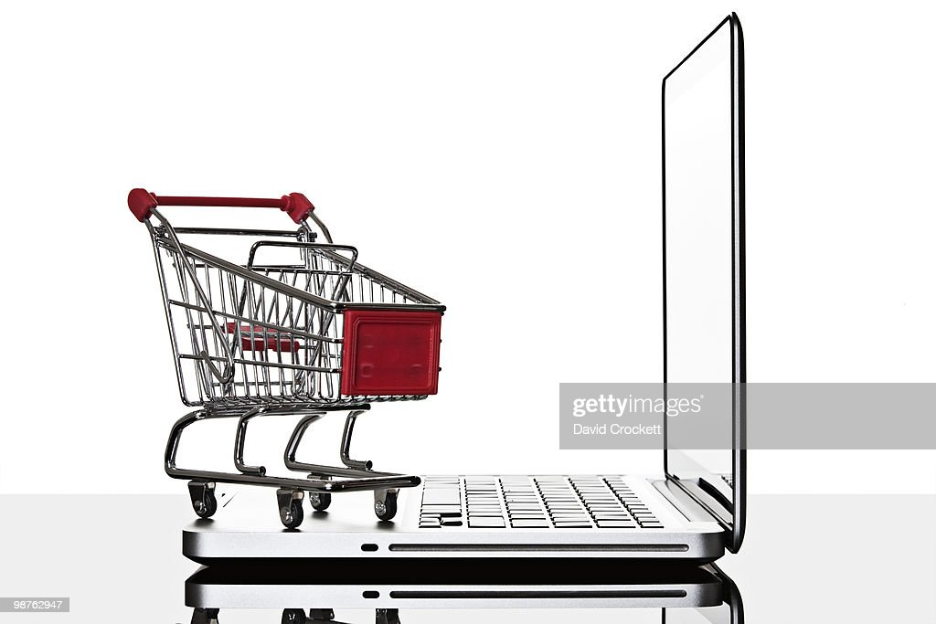 Shopping cart and laptop computer still life : Stock Photo